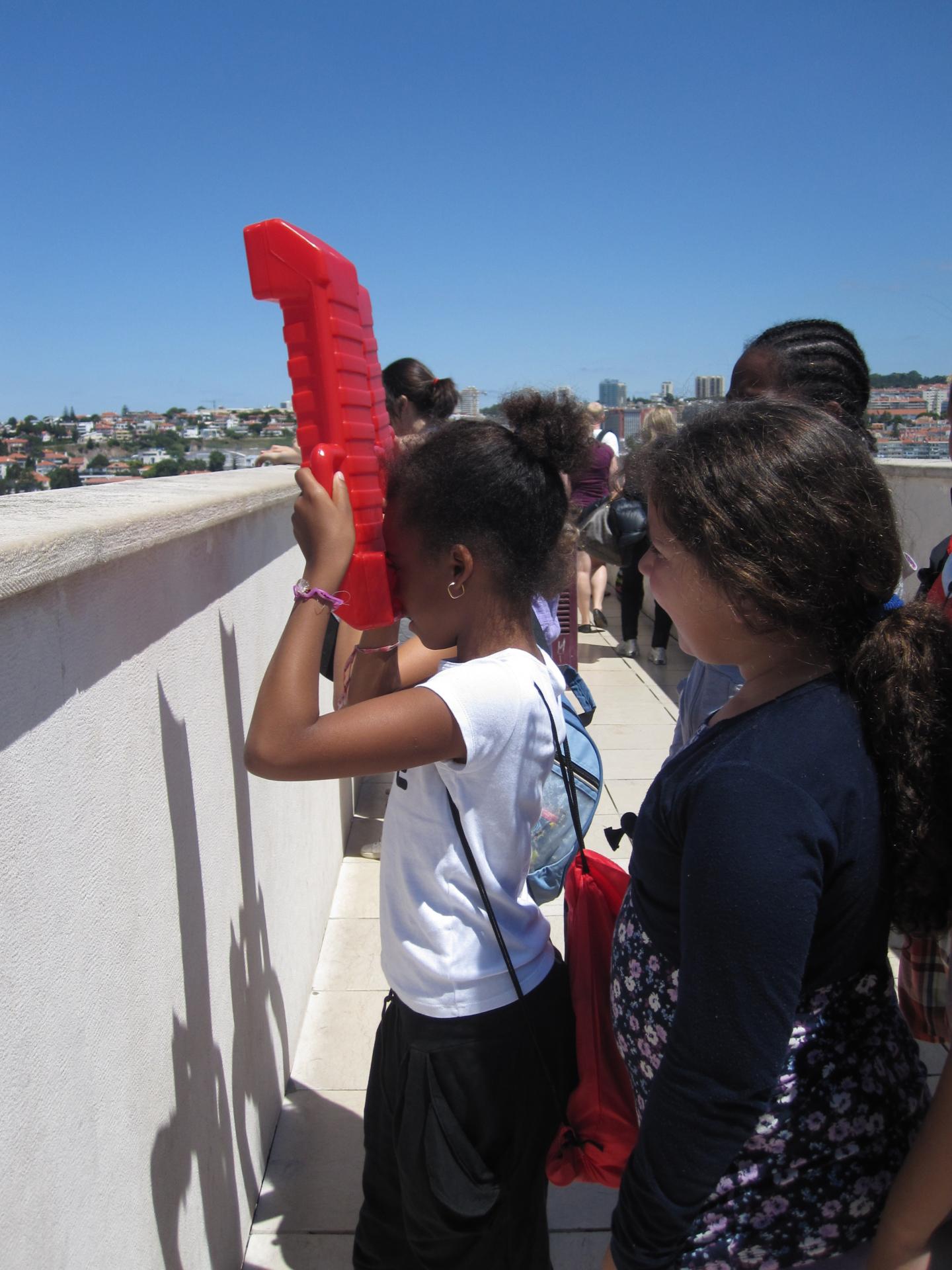 Crianças no miradouro do Padrão dos Descobrimentos com um periscópio