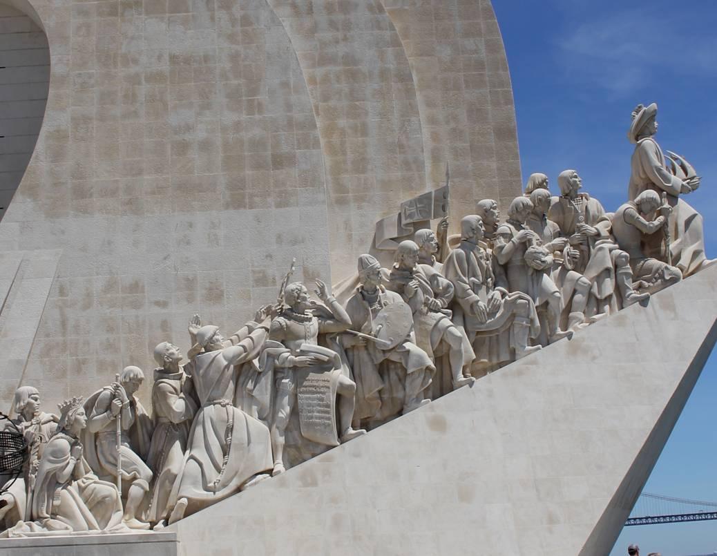 fotografia do lado este do Padrão dos Descobrimentos onde onze figuras da história de Portugal se alinham como se estivessem a subir pelo de encontro à figura do Infante D. Henrique que se encontra no topo do monumento