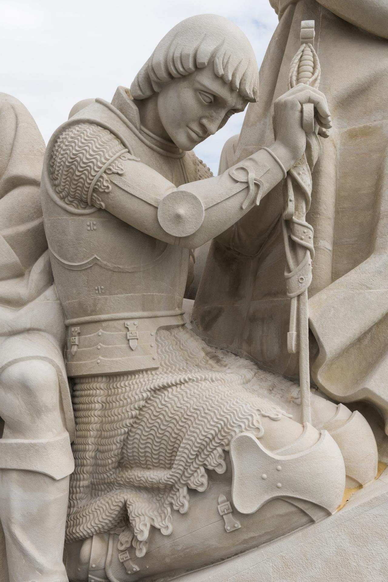 Um homem vestido com uma armadura ajoelhado e debruçado sobre uma espada em posição de obediência