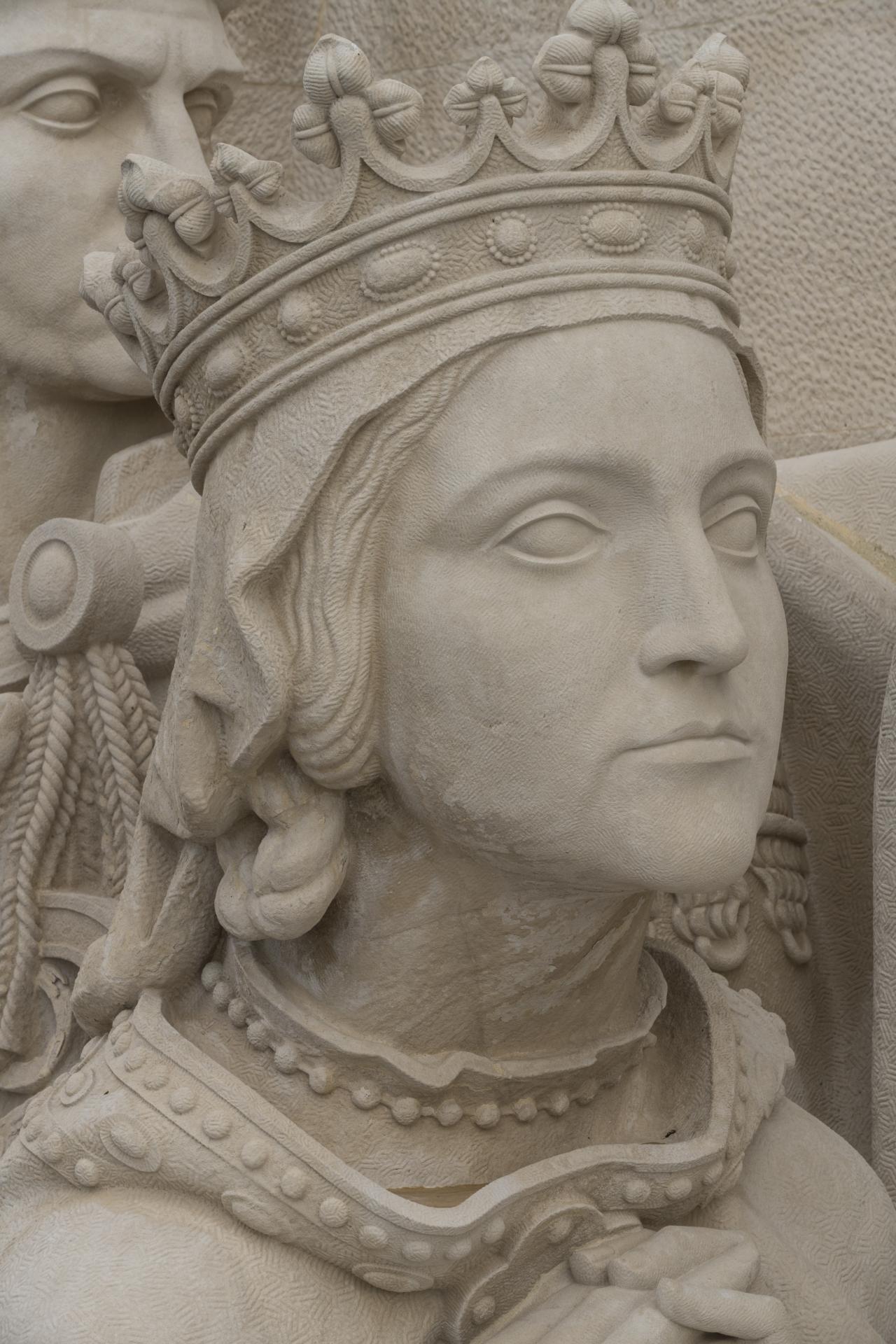 Escultura da face de uma jovem Rainha com uma coroa que prende um véu