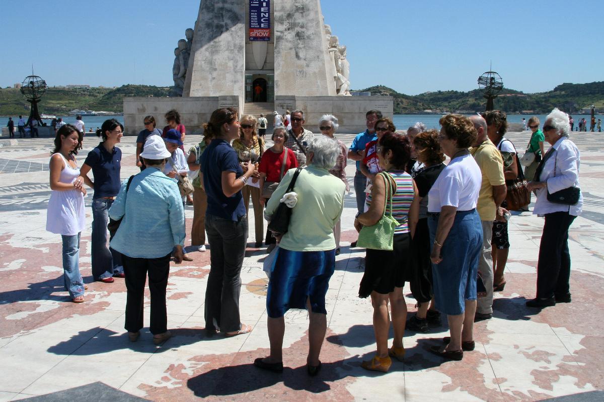 Um grupo de pessoas de pé na Rosa-dos-ventos ouve a descrição do funcionário do Serviço Educativo do Padrão dos Descobrimentos a descrever o monumento