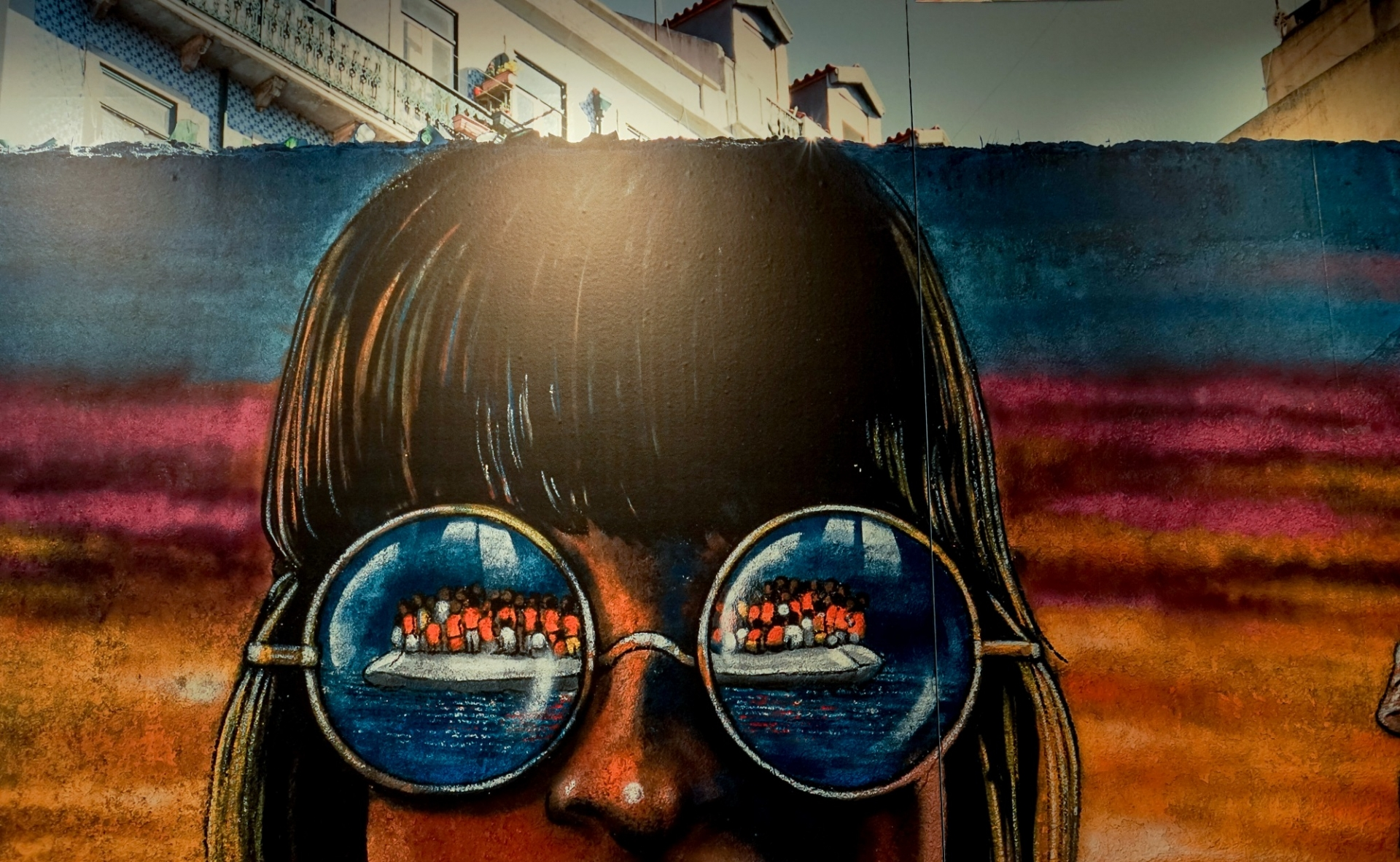 Mural with drawing of a girl in which a boat with migrants is reflected in her glasses