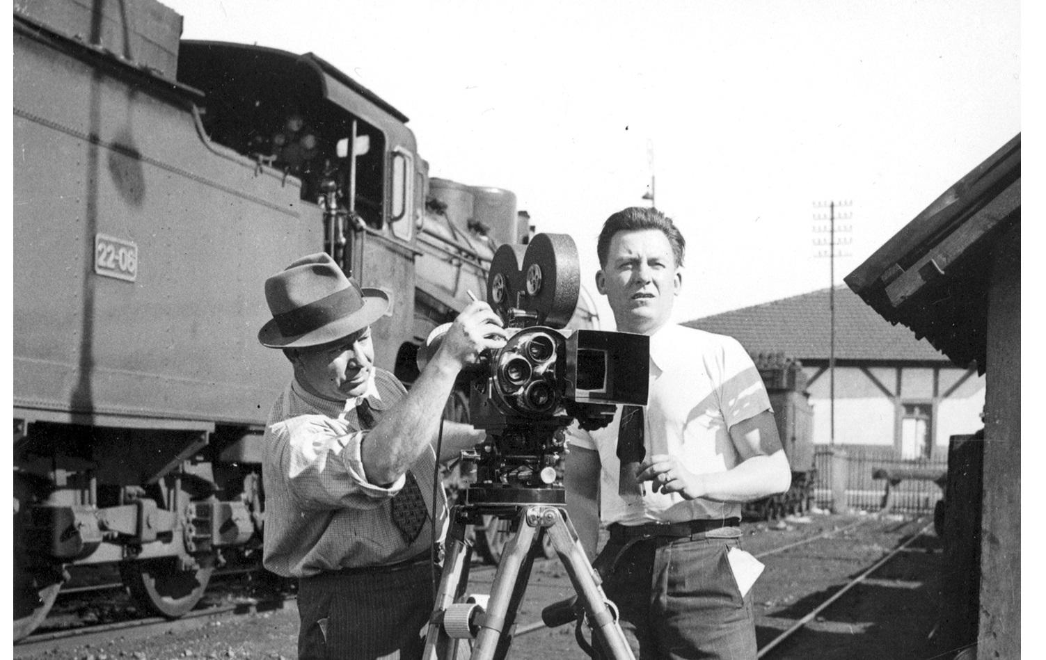 Cottinelli Telmo com uma máquina de filmar de tripé
