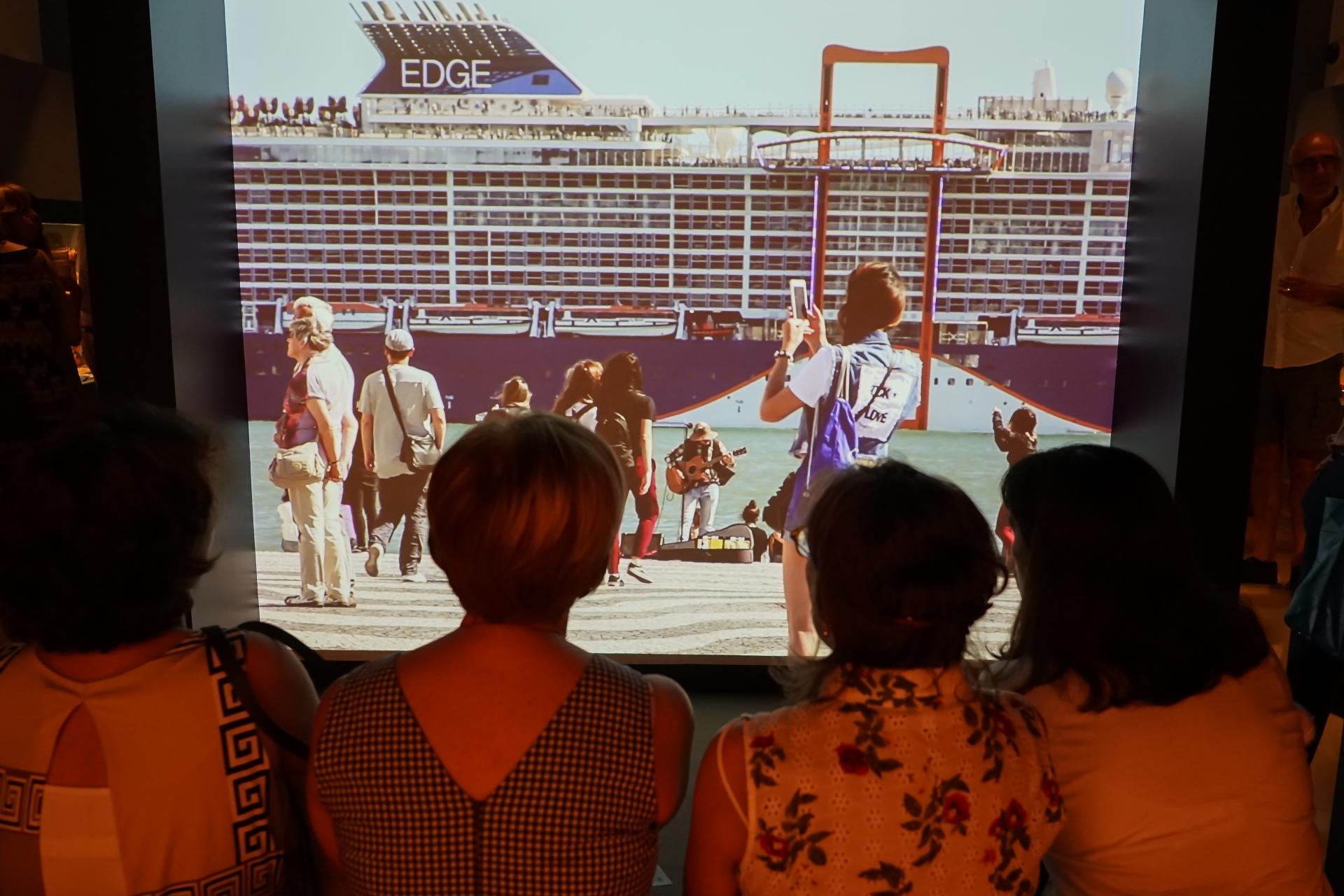 foto de José Frade tirada na exposição Are You a Tourist?. Visitantes da exposição veem o filme  das pessoas e a passear na zona ribeirinha junto ao Padrão dos Descobrimentos