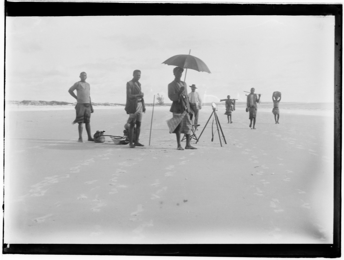 Photograph taken before 1910. Several people on a beach in East Africa, take measurements to place geodesic landmarks.